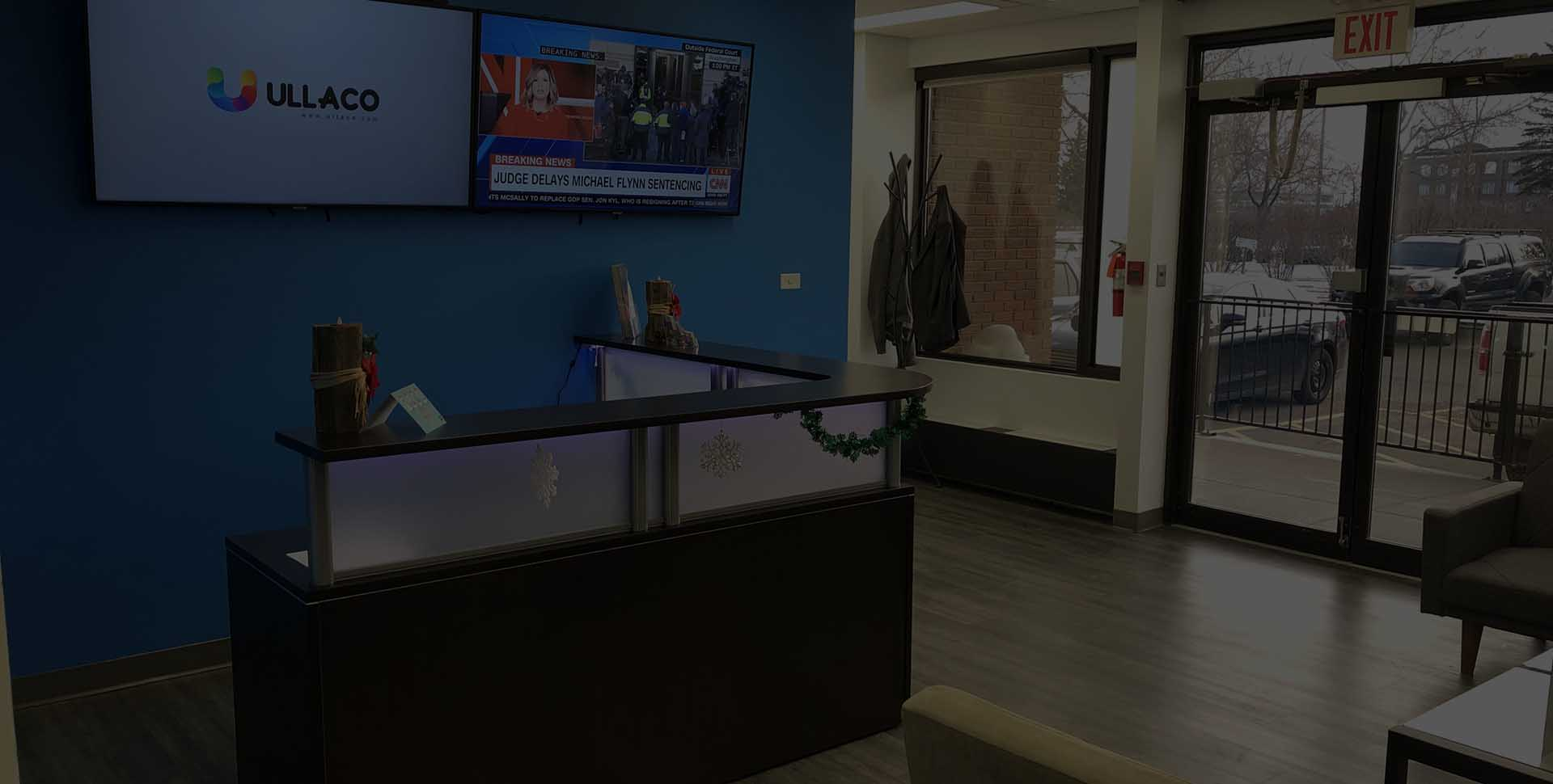 Reception area within our offices. Reception desk and monitors showing CNN and our Logo